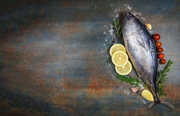 Pescado fresco con hierbas, especias, romero, tomate y limón - pescados y mariscos crudos sobre fondo de placa negra, atún de cola larga, atún pequeño oriental