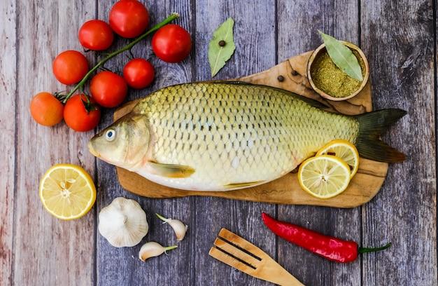 Pescado fresco listo para cocinar. carpa en una cocina de madera tablero en la cocina rodeado de verduras (pimiento, ajo, tomates cherry, limón).