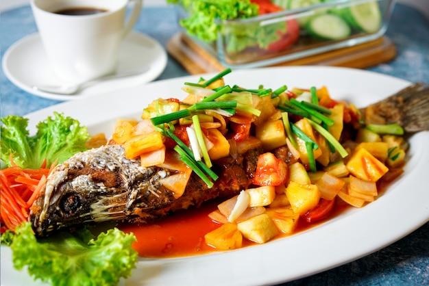 Pescado frito agridulce con mango en una mesa azul con café y taza de café.