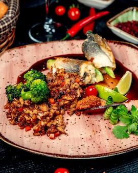 Pescado frito y carne con verduras sobre la mesa