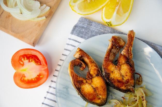 El pescado frito con cebolla está en un plato, sobre una toalla de gofre, al lado hay una tabla de cortar con cebolla picada, limón y tomate sobre un fondo blanco. foto de alta calidad