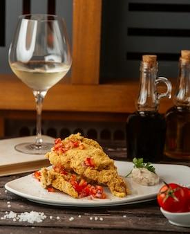 Pescado frito crujiente adornado con cubitos de tomate, servido con salsa de hierbas