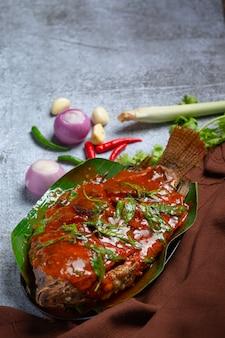 Pescado frito cubierto con salsa de chile, comida tailandesa.