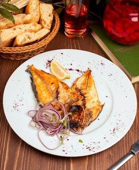 Pescado frito a la parrilla servido en un plato blanco con ensalada de cebolla, limón y hierbas
