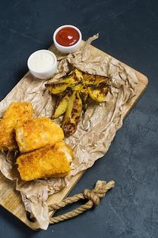Pescado frito con patatas fritas tradicionales ingleses en una tajadera de madera.