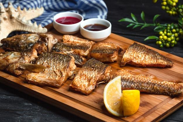 Pescado frito con salsas sobre tabla de madera