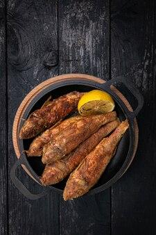 Pescado frito en una sartén de hierro fundido negro sobre una mesa de madera oscura.