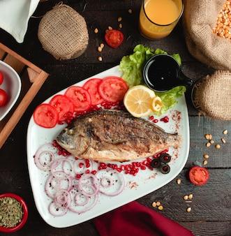 Pescado frito con tomate y cebolla
