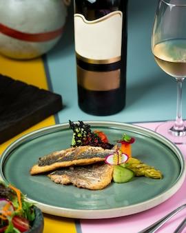 Pescado frito con verduras y una botella de vino blanco.