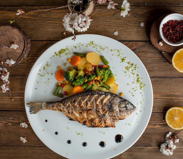 Pescado frito con verduras en el plato