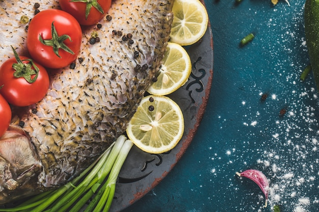 Pescado con limón, tomate y hierbas picadas.