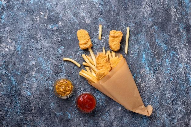 Pescado y papas fritas con salsa de tomate y mostaza.