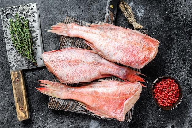 Pescado pargo rojo entero crudo sobre una tabla para cortar