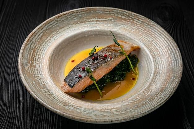 Pescado a la parrilla en un plato sobre una mesa de madera oscura.