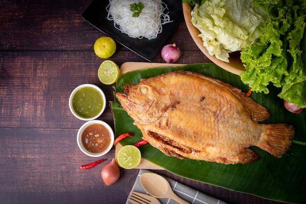 Pescado a la parrilla rústico en la mesa de la cocina, comida tailandesa tradicional.