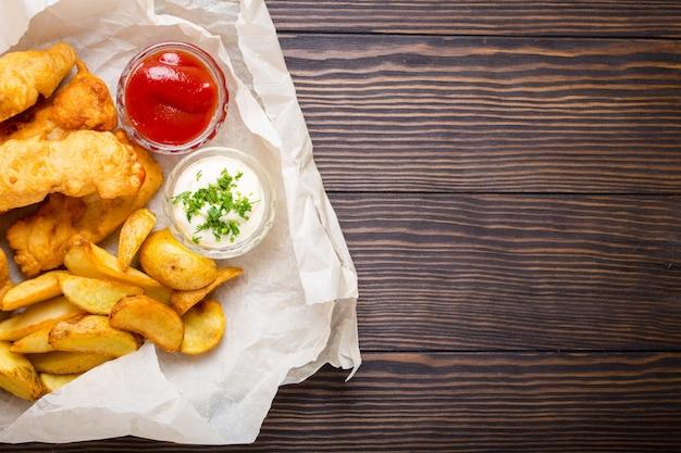 Pescado y patatas fritas de comida rápida tradicional británica con salsas variadas para elegir, sobre papel, fondo de madera rústica