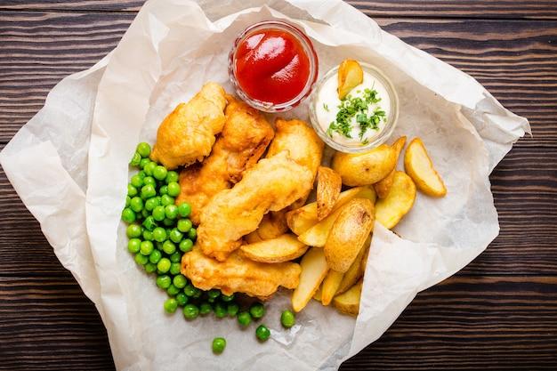 Pescado y patatas fritas de comida rápida tradicional nacional británica con salsas variadas, guisantes frescos, sobre papel, fondo rústico de madera marrón