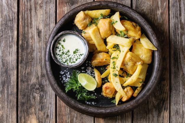 Pescado y patatas fritas con salsa