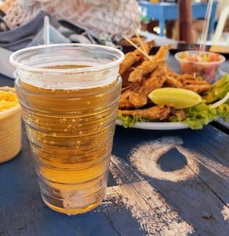 Pescado pequeño frito llamado pilombeta con cerveza en una mesa de bar de playa real snack de playa brasileña