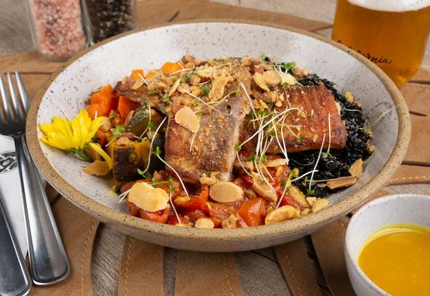 Pescado a la plancha, arroz negro y verduras en un bol con sal, pimienta, salsa y refresco