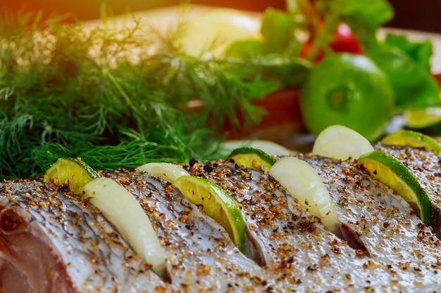 El pescado se prepara para hornear en el horno sobre el filete con cebolla.