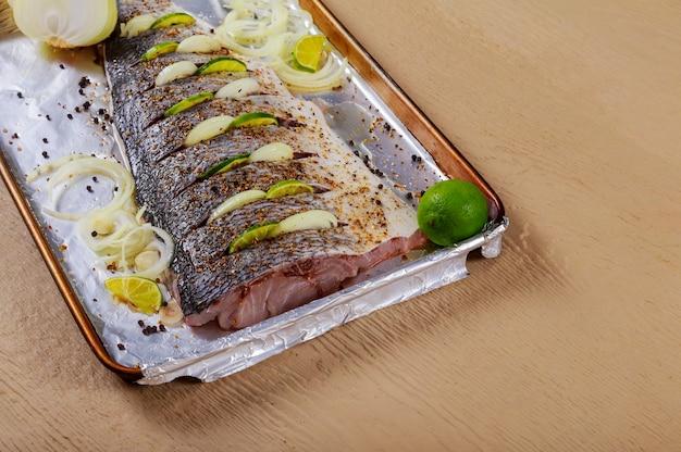 El pescado está preparado para marinar pescado crudo para hornear en el filete con cebolla
