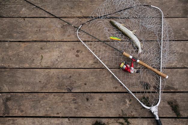 Pescado recién capturado dentro de la red de pesca con caña de pescar sobre el muelle de madera