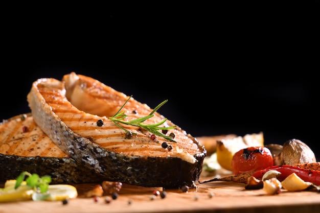 Pescado salmón a la plancha y varias verduras en mesa de madera sobre negro