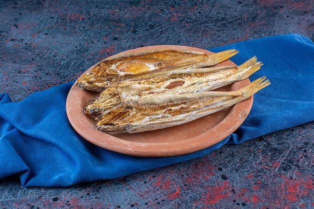 Pescado seco salado aislado en una placa de arcilla sobre una superficie oscura