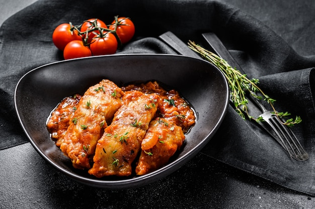 Pescado de tilapia al horno en tomates en un plato. fondo negro. vista superior