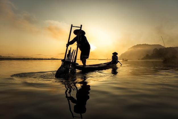 Pescador en acción cuando pesca en el lago, tailandia