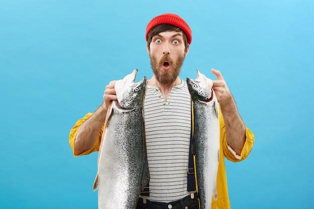 Pescador barbudo guapo posando sobre fondo azul