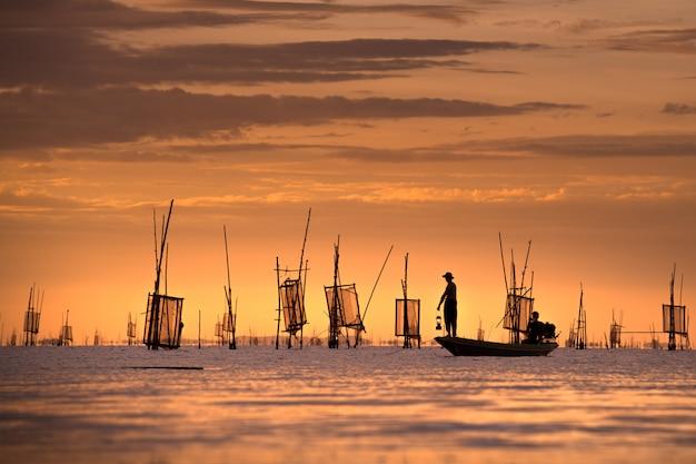 Pescador en el barco de captura de peces con puesta de sol