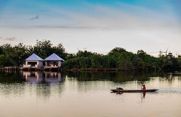 Pescador con bote en el campo del río y el atardecer