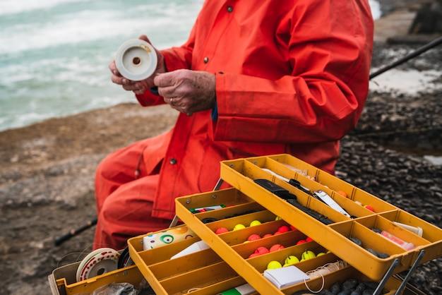 Pescador con caja de equipo de pesca.