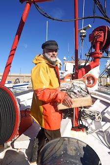Pescador con una caja de peces dentro de un barco de pesca