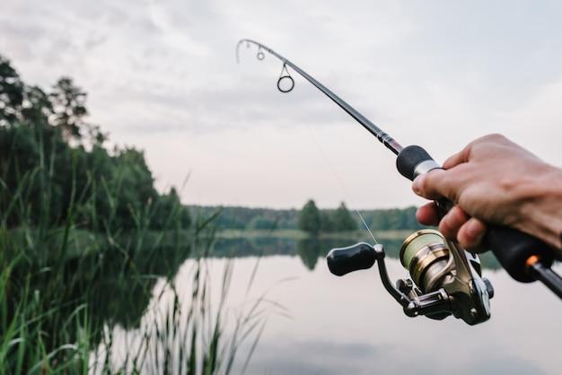 Pescador con caña, carrete giratorio en la orilla del río. el concepto de una escapada rural.