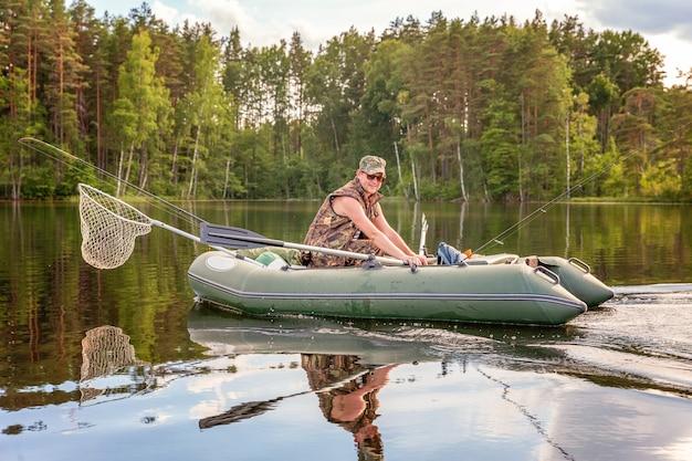 Pescador con cañas de pescar está pescando en un bote de goma en el lago o río