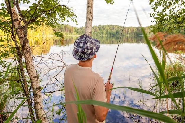 Pescador con cañas de pescar está pescando en un lago o río