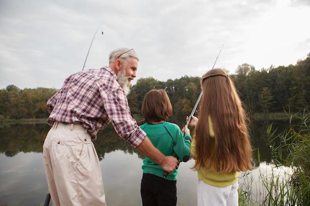 Pescador enseñando a sus nietos a pescar en el lago