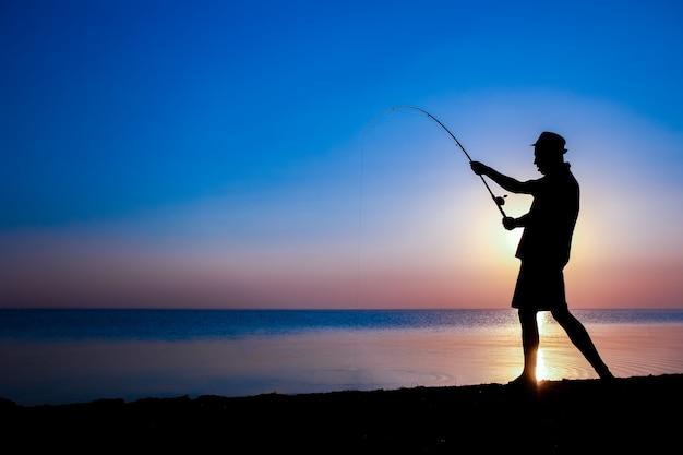 Un pescador feliz pescando peces junto al mar en viajes de silueta de naturaleza