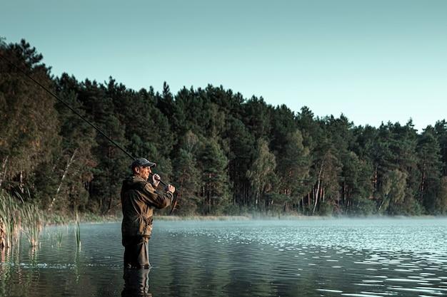 Un pescador masculino en el lago está de pie en el agua y pesca una caña de pescar vacaciones de hobby de pesca