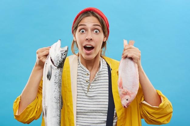 Pescador mujer sorprendida sosteniendo pescado