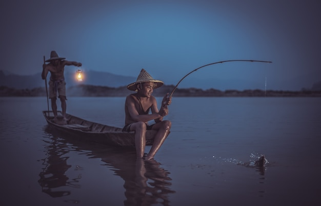 Pescador de los niños con el padre que pesca pescados en el río tailandia del lago