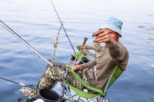 Pescador en el pavimento en el río que muestra la captura. pescado en anzuelo de caña. peces pequeños se ensucian en viajes de pesca.