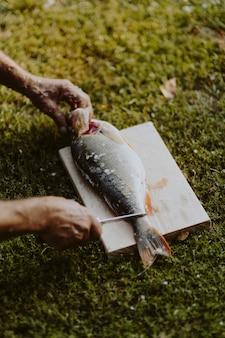 Pescador que sostiene pescados en una tabla de cortar