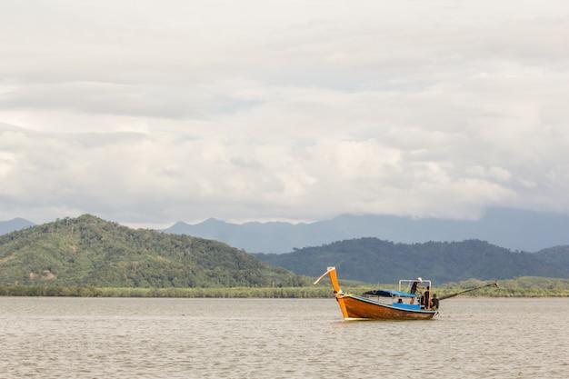 Pescador redes de pesca en el barco de madera.