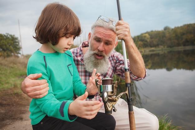 Pescador senior enseñando a su nieto a pescar