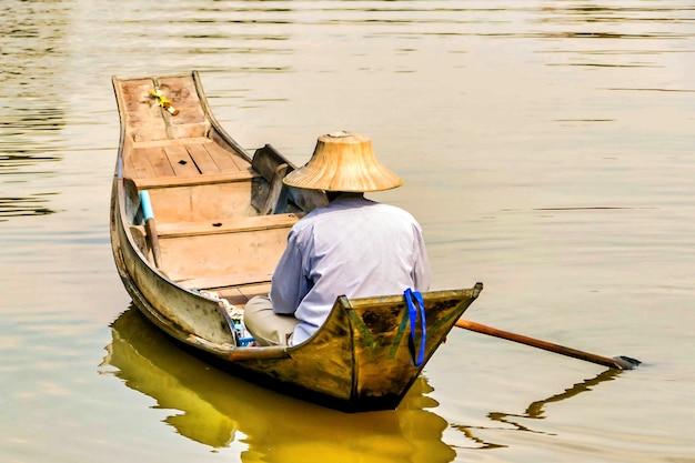 Pescador con un sombrero de cono asiático navegando en el lago con un pequeño bote de madera