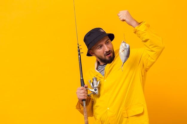 Pescador sosteniendo la caña de pescar y mirando la captura